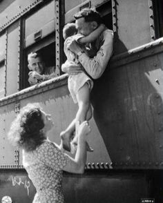 A soldier's wife hoists her son up to a train window for one last good-bye hug from his dad. 1940s.