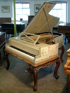 A unique Pleyel grand piano hand-painted with a fairies, satyrs, nudes, monkeys, mythical creatures, birds, flowers and crested composers names. Signed by G. Meunier. Interesting carved fish on piano cheeks. Carved lions head on lid lock. Carved bevelled edge on lid. Piano case sits on ornately carved french walnut frame, carved with foliage and flowers. Piano has six cabriole legs with scroll feet. #uniquepiano #artcasedpiano