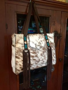 The Buckaroo Tote with Indianhead and buffalo nickel conchos on the straps with turquoise leather lace stitching. The side pockets are lined in suede and the fringe is hand cut. Lined with interior pockets. gowestdesigns.us