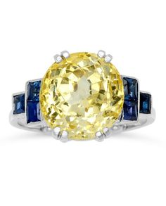 An Art Deco Yellow Sapphire and Sapphire Ring. Centring an oval yellow sapphire weighing approximately 7.75 carats, amid trios of sapphires accenting stepped geometric shoulders, deep openwork gallery, mounted in platinum. #ArtDeco