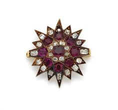 Antique Gold, Ruby and Diamond Starburst Brooch Centering one cushion-shaped ruby encircled by old-mine cut diamonds, further encircled by 8 cushion-shaped rubies, altogether approximately 3.50 cts., the tips of the rays set with 15 cushion-cut diamonds, totaling 23 diamonds approximately .85 ct., one diamond missing, approximately 9.3 dwt.