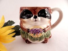 "Adorable whimsical raccoon mug by designer Mary Ann Baker Hand painted ceramic manufactured my Otagiri, made in Japan The cute bandit eyed animal is wearing a green grass skirt and is holding a basket of purple flowers.   3 1/2"" h x 3 1/2"" ..."