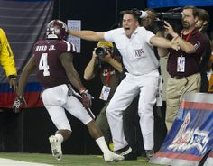 Aggie Yell Leader Roy May shows his excitement as Aggie defender Tony Hurd Jr. returns an interception for a touchdown to win the 2013 Chick-fil-a Bowl.