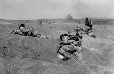 Two U.S. Marines, slumped in death, lie where they fell on Iwo Jima, among the first victims of Japanese gunfire as the American conquest of the strategic Japanese Volcano Island begins on Feb. 19, 1945 during World War II.  (AP Photo/Joe Rosenthal) #