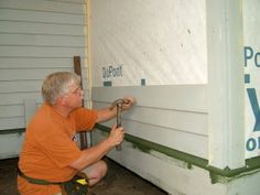Installing wood siding takes time and is not hard to do. Note the painted ends of the pieces behind my head. Each end is painted before the siding is nailed to the wall. PHOTO BY: Kathy Carter