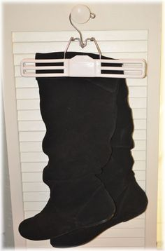 Hang your boots with stick on hooks on your closet wall with a skirt hanger!