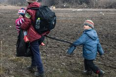 A child strapped with his mother walks with other migrants and refugees after crossing the...
