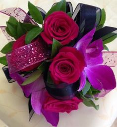 Wrist corsage includes hot pink spray roses, purple dendrobium orchids and fuschia and black ribbon HC1312