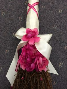 Jump the Broom with this gorgeous wedding accessory.  Cinnamon brown broom adorned with ivory ribbons and pink flowers.  Beautiful!