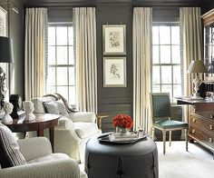 A cozy pair of white armchairs and a tailored pewter-gray ottoman offer a comfy reading spot in this elegant sitting room dotted with black and silver accents. Drapes are of creamy wool and the Greek key trim adds an element that is both masculine and traditional to a color that can be a bit contemporary.