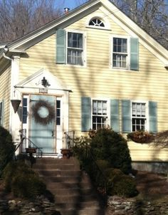 Green-blue shutters & door for yellow house