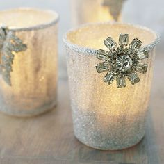 flea market costume jewelry to dress up plain votive cups. Coat glasses with clear crafts glue, then roll the glasses in clear glitter. Attach silver trim around the rims and finish with faux jewels. Light the candles and watch the ensembles sparkle.