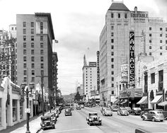 "In this 1938 photo, we can see Hollywood Boulevard looking west from Argyle Ave. ""Vivacious Lady"" starring Ginger Rogers and Jimmy Stewart is playing at the Pantages Theatre, and the streetcar tracks are clearly visible on the road. And look at that cute like of stores where the huge W Hotel is now. Back in the late 1930s, it was the showroom of a used car lot run by the Dodge Brothers."