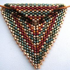 This stunning peyote triangle pendant hangs from a simple cable choker. Nothing complicated here; everything fantastic. ;)  The sides of the triangle are just short of 1.75. It hangs 1.5 long. It was crafted in peyote stitch using Japanese delica beads in galvanized gold, metallic green, silver lined orange, and red. The colors were inspired by a photograph of fallen ginko leaves, taken by etsys very own blockpartypress.etsy.com - http:\/\/www.flickr.com\/photos\/blockpart...