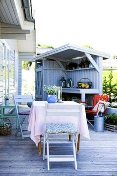 Terrassen er lekkert innredet med stoler som er malt i ulike farger. I bakgrunnen ser vi en liten avdeling med benk og hyller med lykter, potteplanter og frukt.