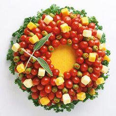 Tomates, azeitonas e queijos arrematados com ervas em um formato circular. Pronto! Aí está uma guirlanda de Natal comestível e linda para uma mesa de aperitivos.