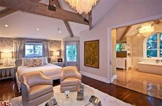 A cathedral ceiling with exposed beams adds rustic elegance to the master bedroom. The luxurious suite includes a spacious bathroom, a fireplace and an adjacent balcony