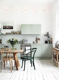 kitchen with mint green cabinets, marble slab backsplash, light wood floors, wooden table surrounded by mismatched light wood and green chairs