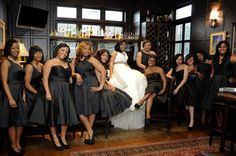The bride wearing a ruffled wedding dress and her bridesmaids wearing short black dresses pose at the bar before the wedding.
