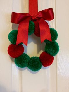 A handmade pom pom wreath with 9 acrylic wool pom poms in a Christmas colour scheme of red and green. The pom poms are 5cm in size and the wreath is approximately 18cm excluding the bow. This makes a perfect Christmas decoration to hang around the home or for parties and events. The pom poms are fixed to an embroidery hoop, neatly finished on reverse with wool felt and the bow is handmade with satin ribbon. The wreath is made to order and can be made in different colours, if you would like…