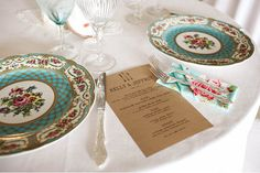 """vintage plates with """"peacock-like colours. I would use pale blue, pink & green budvases, white candles, and deep pink florals as the centerpieces."""