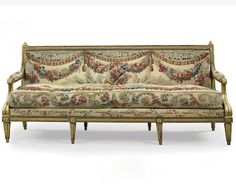A LOUIS XVI GILTWOOD CANAPE  BY CLAUDE II SENE, CIRCA 1780  The back and seat with loose cushion covered in contemporary Beauvais tapestry upholstery, the frame carved with entrelacs, the tapestry woven with floral swags and trophies on fluted tapering legs, 88 in. (223.5 cm.) wide