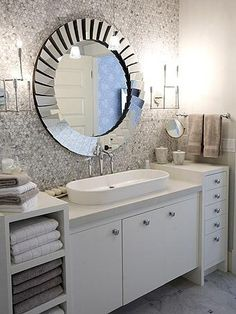I love the white cabinetry with the shimmery tiles and the exquisite large, round wall mirror.  It's a dazzling bathroom.