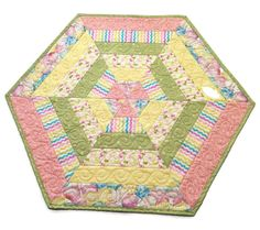 Adorable Easter Egg Hexagon Table Topper will fit most flat surfaces, and is especially nice on a round or square table. Just in time for Spring, and Summer Decorating! It can be used as a candle mat, too! Its all in your favorite summery colors with lots of yellow and pink.  SIZE and FEATURES: --25 1/2 side to side, 29 1/2 wide point to point. --Back is a coordinating pink and green print - see the photos --Quilted all over with delightful swirls and lots of stitching in the ditch ...