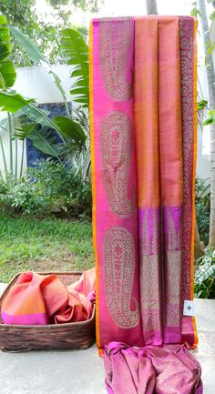 This punch pink Benares tussar is striped with gold yellow. The border and pallu are in magenta with large patterns in gold zari giving this traditional attire a modern twist