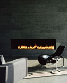 Modern Fireplace Design at Home Living Room on Stone Tile Wall decor with Black Chair and Unique Chrome Sideboard