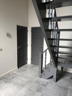 """Hal die rust uitstraalt: Grijze deuren in witte kozijnen en grijze trap. Plinten en kozijnen in dezelfde kleur als de wanden. Vloertegels van Rex """"de la roche""""."""
