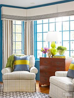 This bay window offers a triple dose of flair with its electric blue-painted trim and walls, multipane windows, and neat window dressing. The window treatment, working as a singular unit, combines a traditional valance with drapery. Solid neutral fabrics trimmed in Greek-key banding add interest while balancing out the strong visual punches in this cozy vignette.