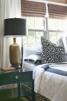 Black-and-white animal print pillows and a matching bed skirt add movement to the otherwise tailored look of designer Dayka Robinson's own bedroom. Bamboo shades and a hammered brass lamp lend warmth and textural interest. Design by Dayka Robinson Designs Bed Infront Of Window, Woven Wood Shades, Bamboo Shades, Master Bedroom, Bedroom Decor, Bedroom Ideas, Bedroom Designs, Bedroom Photos, Amber Interiors