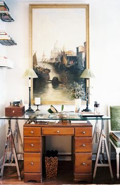 by layering a piece of glass over a family heirloom desk from his grandfather, matthew re-purposed a fairly basic looking desk creating an amazing conversation piece and catch-all for his collections. i love the unexpected industrial-looking metal sawhorse legs supporting the glass over the desk, and leaving that great little space for books and collectibles.   love love love this idea. and the styling.
