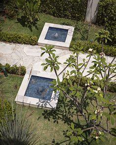 Casa é rodeada por jardim com flores, horta e caminhos delicados