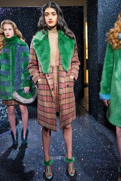 Hannah Weiland - A/W 2015, Womenswear, via glamourmagazine.co.uk  This garment, with the influence of the wizard of Oz, incorporates a tactile element with  the fur and a visually tactile one with the tartan. The green on the lapel and shoes break up a solid, structural coat. The lapel travels your eye downwards and the tartan moves it across and around the body.