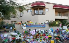 """A view of the grassroots tribute memorial at Congresswoman Gabrielle Giffords' office which spontaneously grew after the shootings of Giffords and 18 others at her """"Congress on Your Corner"""" event on January 8, 2011 in Tucson, Arizona. Six people perished in the attacks. Photo by Kevin C. Cox/ Getty Images."""