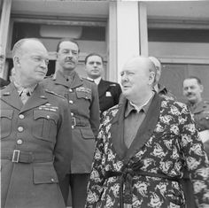 The Prime Minister Winston Churchill, dressed in his siren suit and dressing gown, stands beside General Dwight D Eisenhower, with General Harold Alexander behind them, at his headquarters in Tunis, Tunisia, on Christmas Day, 25 December 1943. (Imperial War Museum/History By Zim)