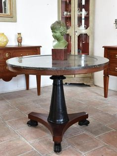 """This exceptionally rare round black marble table would make a striking statement in an entry foyer. It dates to the start of the 19th century. The black marble top has a lip around the edge and the three mahogany legs sit on lion feet with castors. 38¼"""" diameter x 30¼"""" high 97cm diameter x 77cm high"""