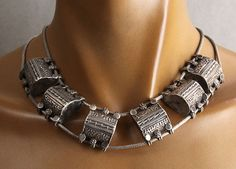 A short necklace made of a set of six antique silver amulet boxes from Yemen, strung on a linkless Indian chain.