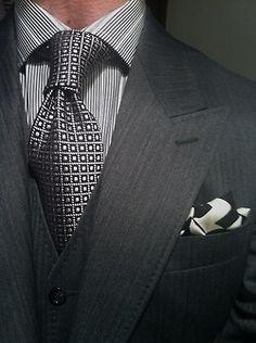 グレースーツに幾何学模様のタイとチーフを合わせた着こなし