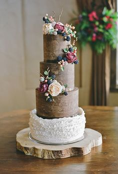 Brides.com: . To complement the bride's earthy-yet-sophisticated wedding aesthetic, Sonja McLean of Sweet and Swanky Cakes made this rustic-looking cake, which took more than 80 hours to create. Chocolate ganache was applied to the tiers to achieve a wood grain effect, while the ruffles added a romantic touch. The entire cake was covered in peonies, ripe blackberries, twigs, and hypericum berries, all sculpted from fondant and sugar.   $16 per slice, Sweet and Swanky Cakes