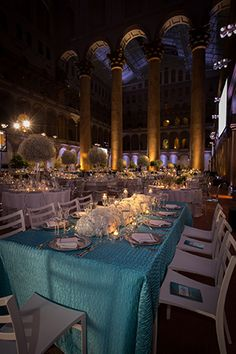 Tutera used light blue linens, evocative of the night's printed program, in one of the four table designs with all white hydrangeas and candles at the center.