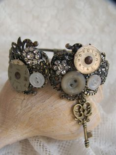 Vintage Style Bracelet made from an ornate, filigree cuff which opens in the front, and a hinge in the back. It is covered with many antique watch faces,