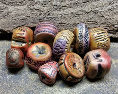 Eclectic collection of 10 beads with a variety of organic and digital patterns. Shades of rusty red, yellow ocher, purple, and black. Highlights of golden metallic bronze. Largest diameter: 3/4 Thickest bead hole to hole: 1/2 Holes approximately 1.5mm.