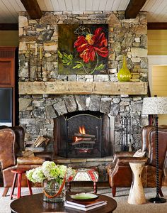 Leather wing chairs from Holland & Co. sit in front of this cozy hearth with a rustic mantel - Traditional Home®  Photo: Emily Followill