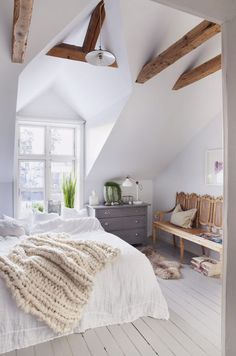 airy bedroom with beams, oroccan wedding quilt, crocheted throw, bench with tall back
