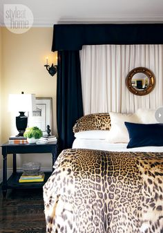 The black-and-white palette adds crispness to the bedroom, with its sumptuous leopard-print bed linens and softly draped bed curtains. A nautical-inspired mirror above the bed focuses the composition.