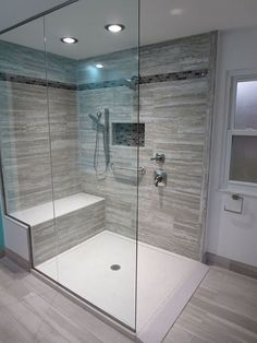 """The Gray Jewel tile is accentuated by the twill blend stripe and niche. The seat and base are solid surface in blizzard. The glass was custom made and goes to the ceiling. The shower overall is 48x72"""" - walk in modern shower gray bathroom"""