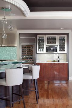 In this glam kitchen, custom features abound, including a spacious built-in wine cooler and a textured glass backsplash. Glass-front cabinets put drinkware on display, and an elevated glass countertop on the island gives the space an overall modern feel. A rich chocolate brown in the inset ceiling warms and balances the room.
